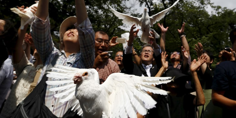 People release doves as a symbol of peace at Yasukuni Shrine on the anniversary of Japan's surrender in World War Two in Tokyo, Aug. 15, 2015. (Thomas Peter/Reuters)