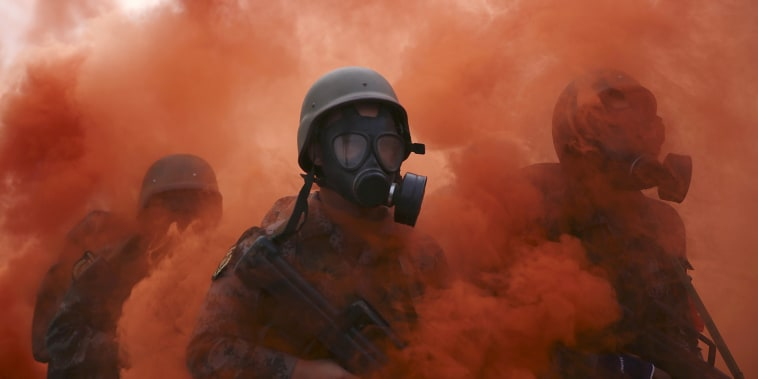 University students in military uniforms and gas masks walk past chemicals billowing from canisters, during a special military training in Beijing, China, Sept. 21, 2015. (Reuters)