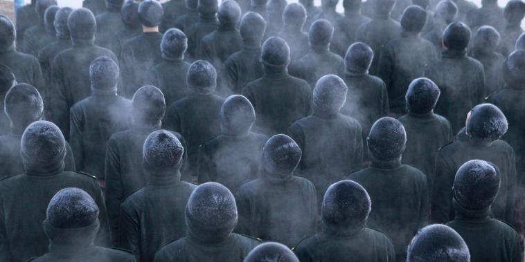 New recruit People's Liberation Army (PLA) soldiers stand in formation during a training session in cold winter temperatures at a military base in Heihe