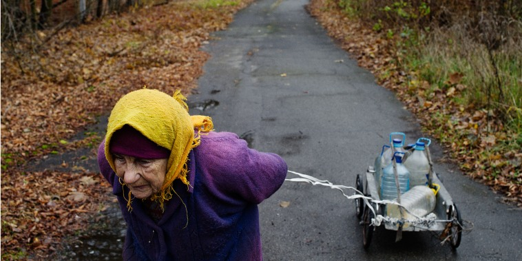 A babushka walks along a deserted road, drawing behind her water she's fetched from a city well. (Photo by Guillaume Herbaut/INSTITUTE)