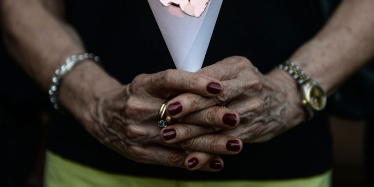 A member of the French community holds a candle during a vigil in Bangkok on July 15, 2016. (Photo by Lillian Suwanrumpha/AFP/Getty)