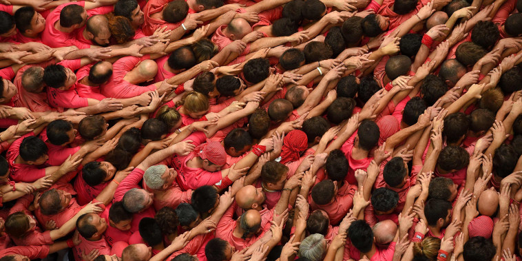 """Members of the \""""Colla Vella dels Xiquets de Valls\"""" human tower team form a \""""castell\"""" during the XXVI human towers, or 'castells', competetion in Tarragona, Spain on Oct. 2, 2016. (Photo by Lluis Gene/AFP/Getty)"""