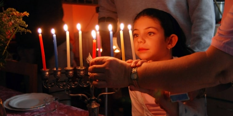 A family is lighting a candle for the Jewish holiday of Hanukkah.; Shutterstock ID 101422984; PO: today.com