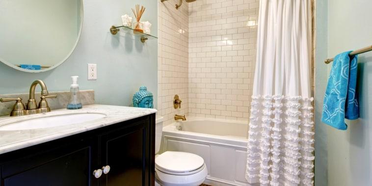 Aqua bathroom with dark floor and tile wall trim. View of bathroom vanity with mirror; Shutterstock ID 197681846; PO: today.com