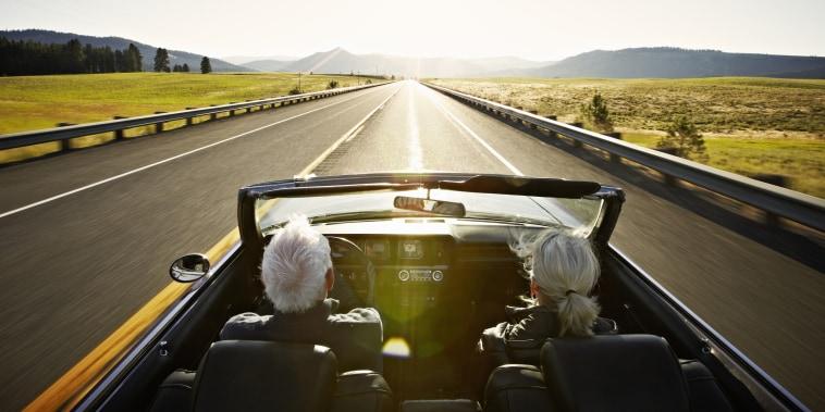 Senior couple driving convertible car at sunrise