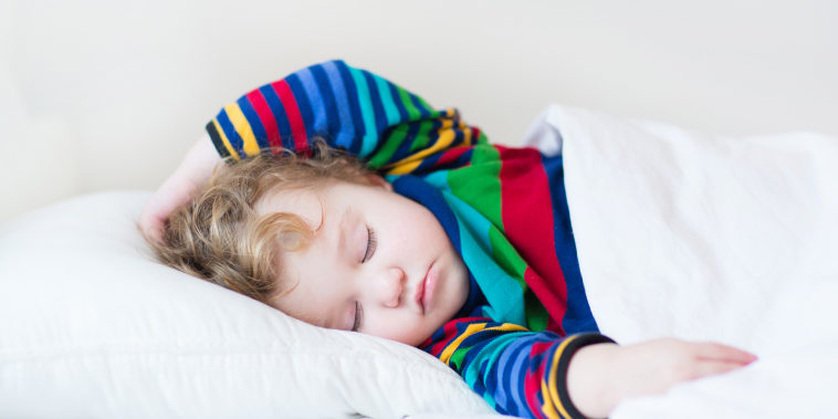 Funny sleeping toddler girl in a white bed
