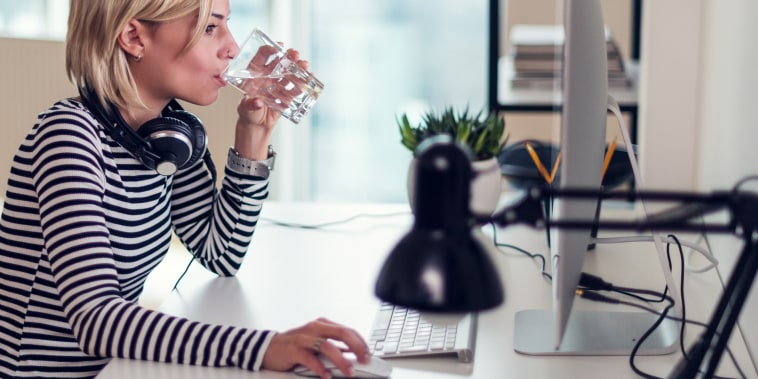 Image: Woman at computer having glass of water