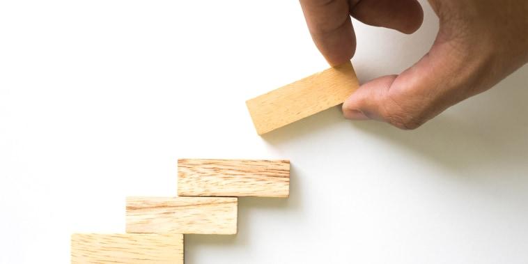 Image: A hand arranges wood blocks