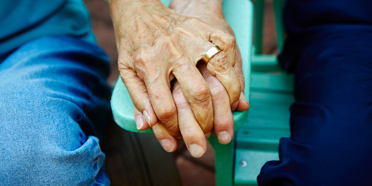 Image: An elderly couple holds hands on a park bench