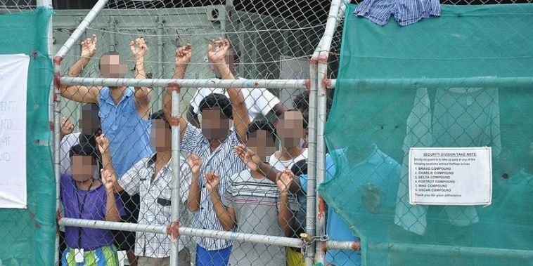 Asylum-seekers look through a fence at the Manus Island detention center in Papua New Guinea on Mar. 21, 2014. Reuters