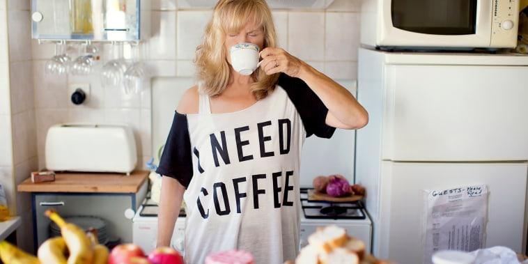 Caucasian woman drinking coffee in kitchen