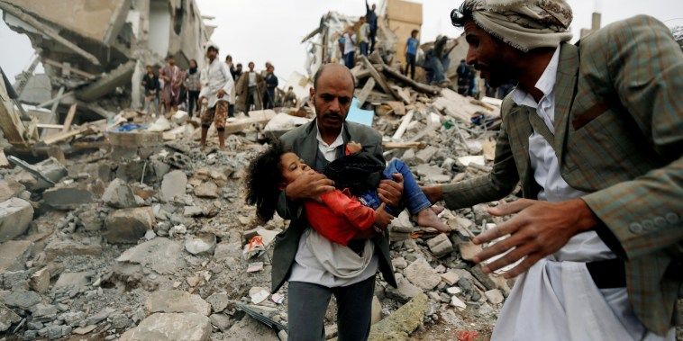 Image: Man carries an injured girl rescued from the site of a Saudi-led air strike in Sanaa