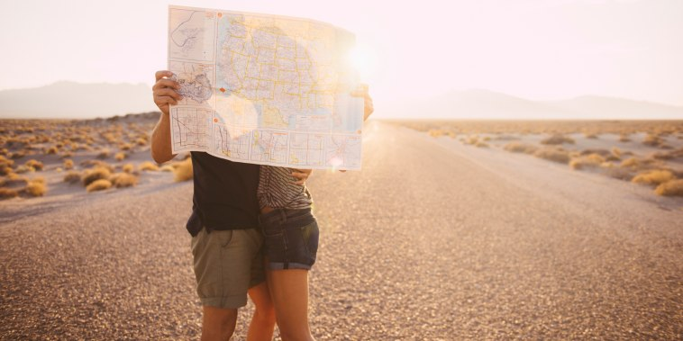 Image: couple kissing behind map on remote road