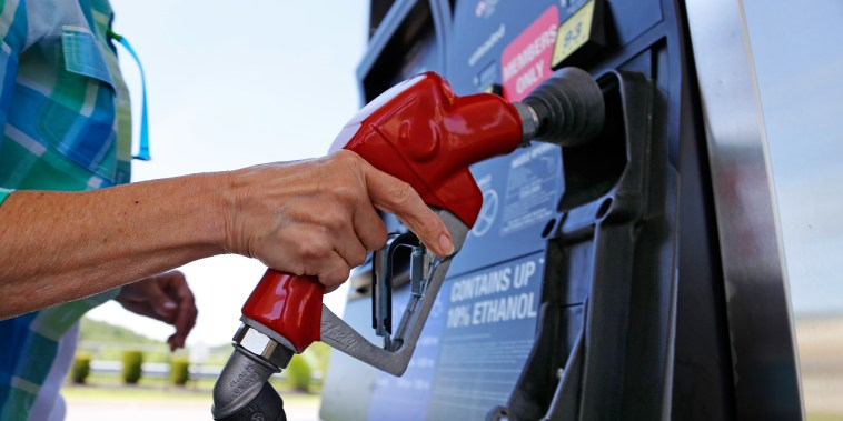 Image: A woman holds a nozzle as she refuels her car