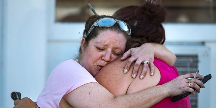 Image: Carrie Matula embraces a woman after a fatal shooting
