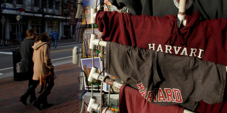 Image: People walk past Harvard University t-shirts for sale in Harvard Square in Cambridge