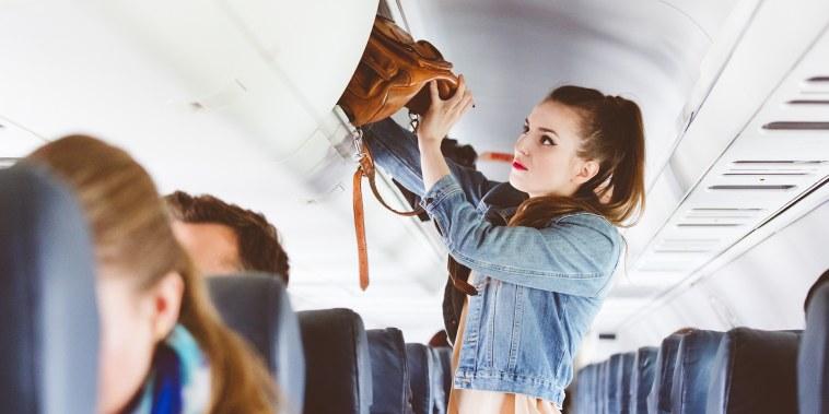 Female airplane passenger storing handbag in locker