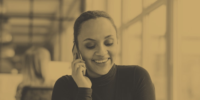 Image: Happy young woman sitting at her desk working and answering a phone call.