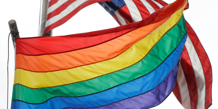 The Rainbow Flag flies beneath the American flag at the Stonewall National Monument, Wednesday, Oct. 11, 2017, in New York. The Rainbow Flag, an international symbol of LGBT liberation and pride, was flown for the first time at the monument. (AP Photo/Mark Lennihan)