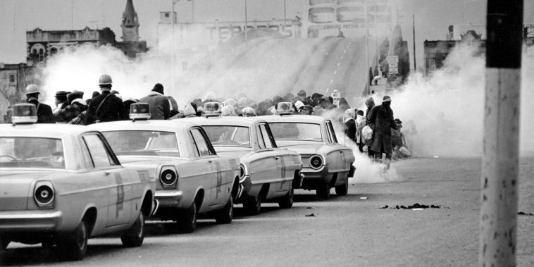 """FILE - In this March 7, 1965 file photo, clouds of tear gas fill the air as state troopers, ordered by Gov. George Wallace, break up a demonstration march in Selma, Ala., on what became known as \""""Bloody Sunday.\"""" The incident is widely credited for galvanizing the nation's leaders and ultimately yielded passage of the Voting Rights Act of 1965."""