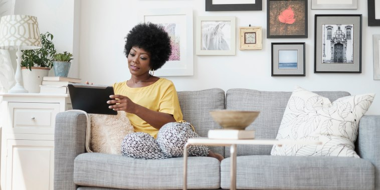 Image: African American woman using digital tablet on sofa