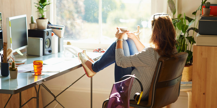 Image: Pensive woman looking through window with feet up on desk in sunny home office