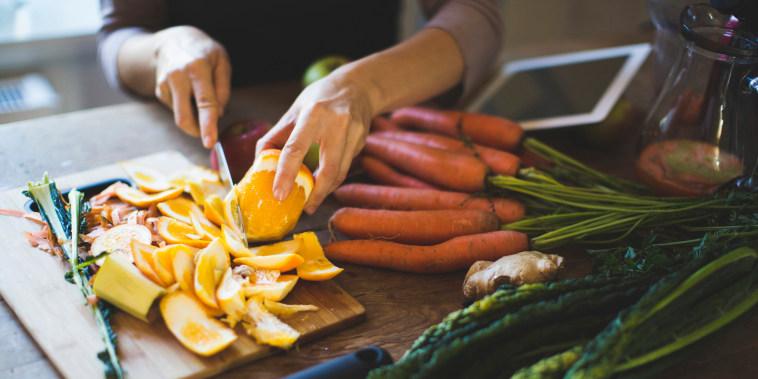 Image: A woman peels an orange on a cutting board