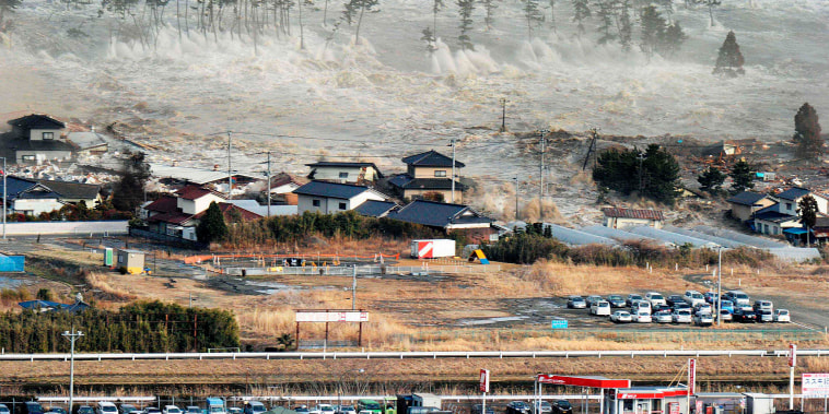 Image: Waves of a tsunami hit residences after a powerful earthquake in Natori, Miyagi, Japan, on  March 11, 2011.