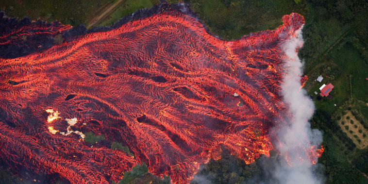 Image: A massive fast moving lava flow consumes everything in its path, as the flames from the remnants of one home burns on the left, while it approaches another on the right in Pahoa, Hawaii, May 19, 2018.