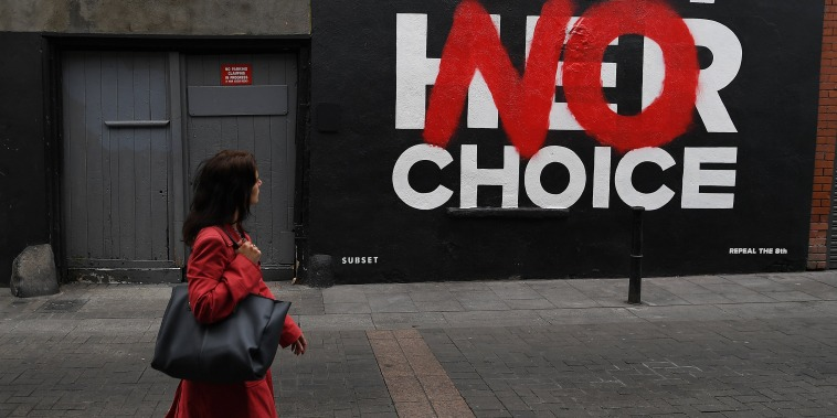 Image: A woman walks past a new Pro-Choice mural by a graffiti artist collective called 'Subset' ahead of a 25th May referendum on abortion law, in Dublin
