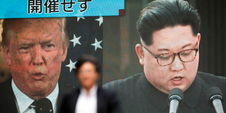 Image: A pedestrian walks in front of a screen in Tokyo showing Donald Trump and Kim Jong Un