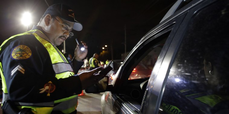 Image: A police officer looks at a driver's license during a drunk-driving checkpoint