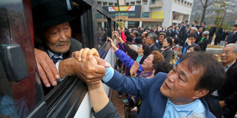 Image: North and South Korean family members hold hands as they bid farewell to each other during the separated family reunions at Mount Kumgang resort