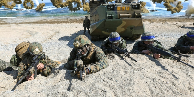 U.S. Marines, left, and South Korean Marines, wearing blue headbands on their helmets, take positions during a joint military exercises in South Korea in 2016.