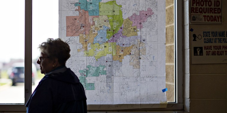Image: A resident stands near a map of local polling places