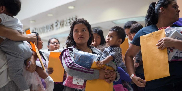 Image: Immigrants wait to go to a Catholic Charities relief center
