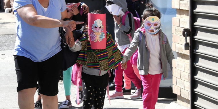 Image: Children, with their faces covered with masks, leave the Cayuga Center, which provides foster care and other services to immigrant children separated from their families, in New York City