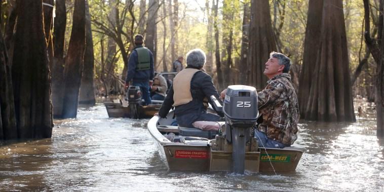 Image: Crawfisherman ride through the Atchafalaya Basin swamp water.