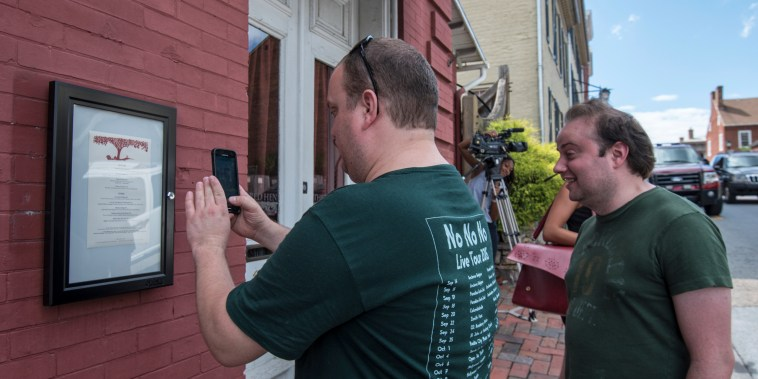 A passerby takes a photo of the menu outside of the Red Hen Restaurant on Saturday in Lexington, Virginia.