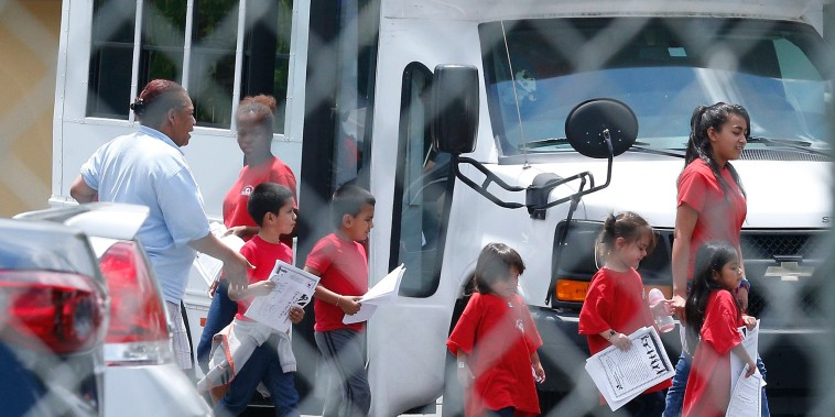 Image: Migrant children walk off a bus at the Catholic Charities' Msgr. Bryan Walsh Children's Village in Cutler Bay