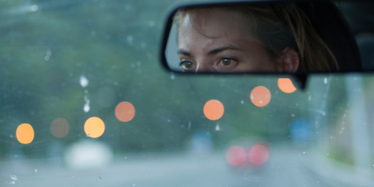 Image: Tired woman driving at dusk on a highway