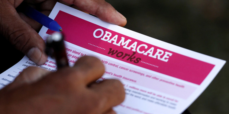 Image: A man fills out an information card during an Affordable Care Act outreach event