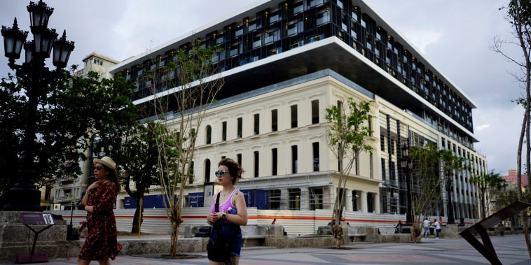 Image: Tourists pass by a hotel under construction at the Paseo del Prado boulevard in Havana