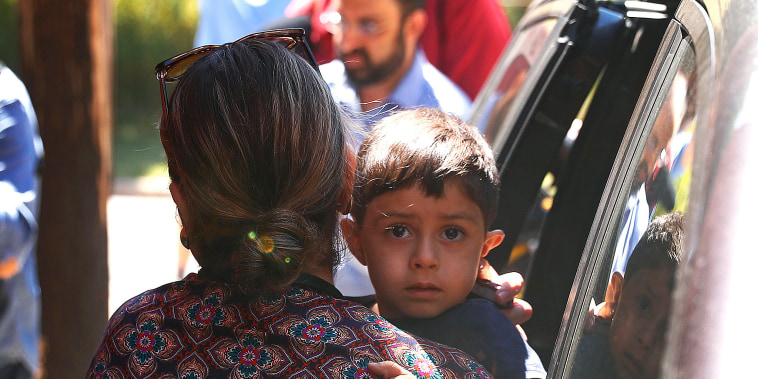 Image: A child from Honduras is brought to the United States Immigration and Customs Enforcement office in Grand Rapids