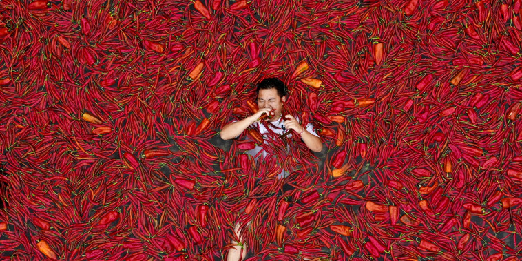 Image: A contestant lays in a pool of red chilies