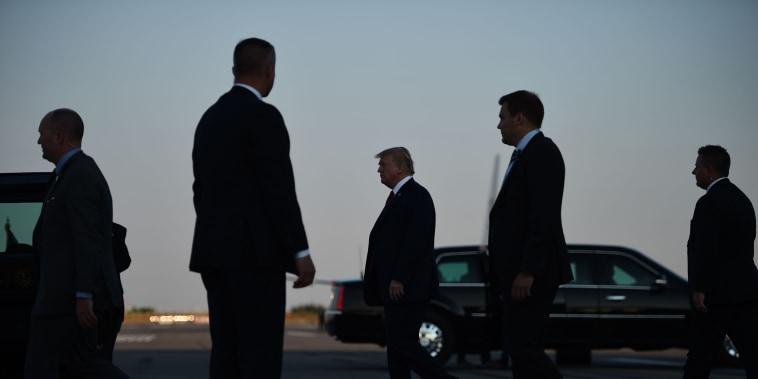 Image: President Donald Trump, center, walks towards the Presidential car upon arrival at Helsinki