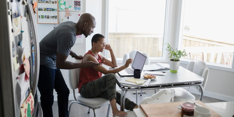 Image: Mature couple using laptop at kitchen table