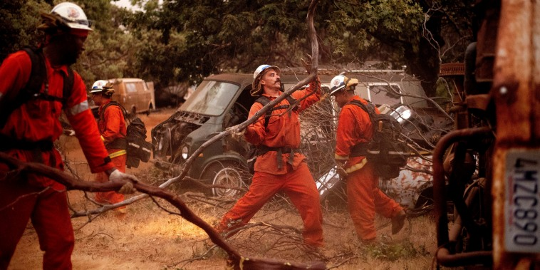 Inmate firefighters clear brush to create a fire break while battling the Ferguson Fire