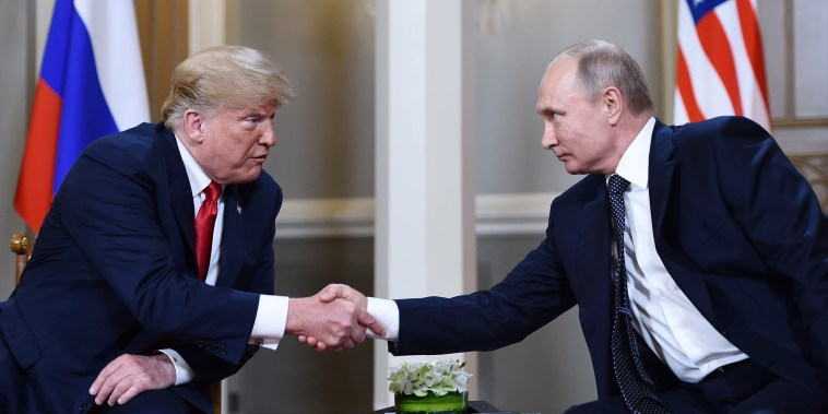 Image: Vladimir Putin  and Donald Trump shake hands before a meeting in Helsinki