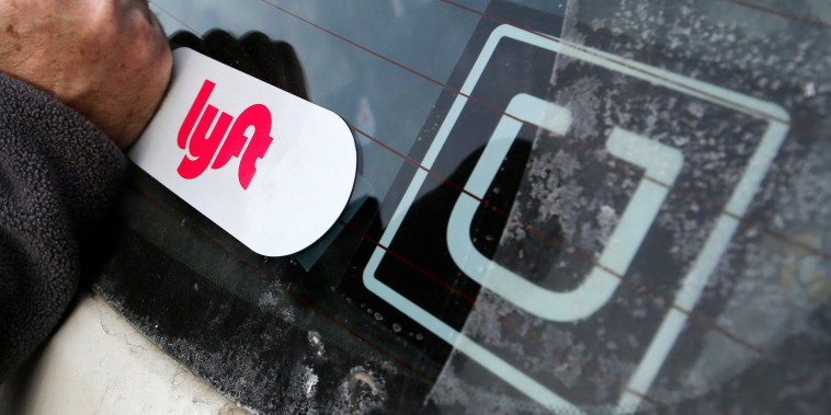 Image: A Lyft logo is installed on a Lyft driver's car next to an Uber sticker